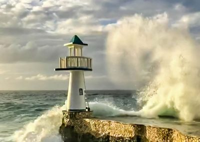 Big waves hitting lighthouse on cliffs in West End, Negril, Jamaica