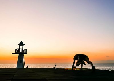 Working out in front of lighthouse and sunset sky in West End, Jamaica