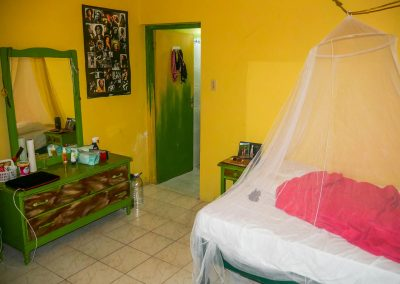 Hotel room with small cupboards and bed with mosquito net in West End, Jamaica