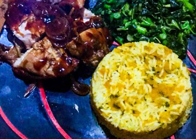 Jamaican food on plate: Jerk chicken, rice and callaloo