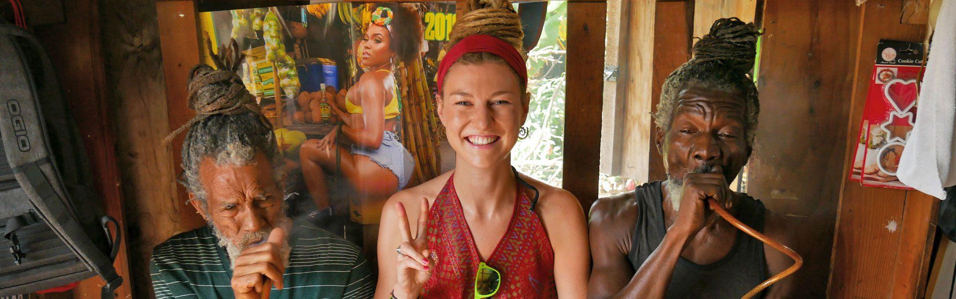 German dreadlock girl with Rastafarians smoking cannabis in Kingston, Jamaica