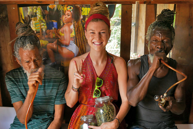 German dreadlock girl with Rastafarians smoking ganja in Kingston, Jamaica