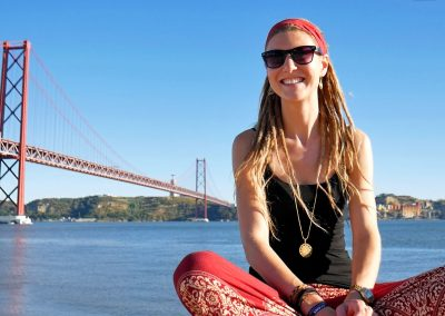 Rasta girl in front of Tagus, Ponte 25 de Abril and Cristo Redentor in Lisbon, Portugal