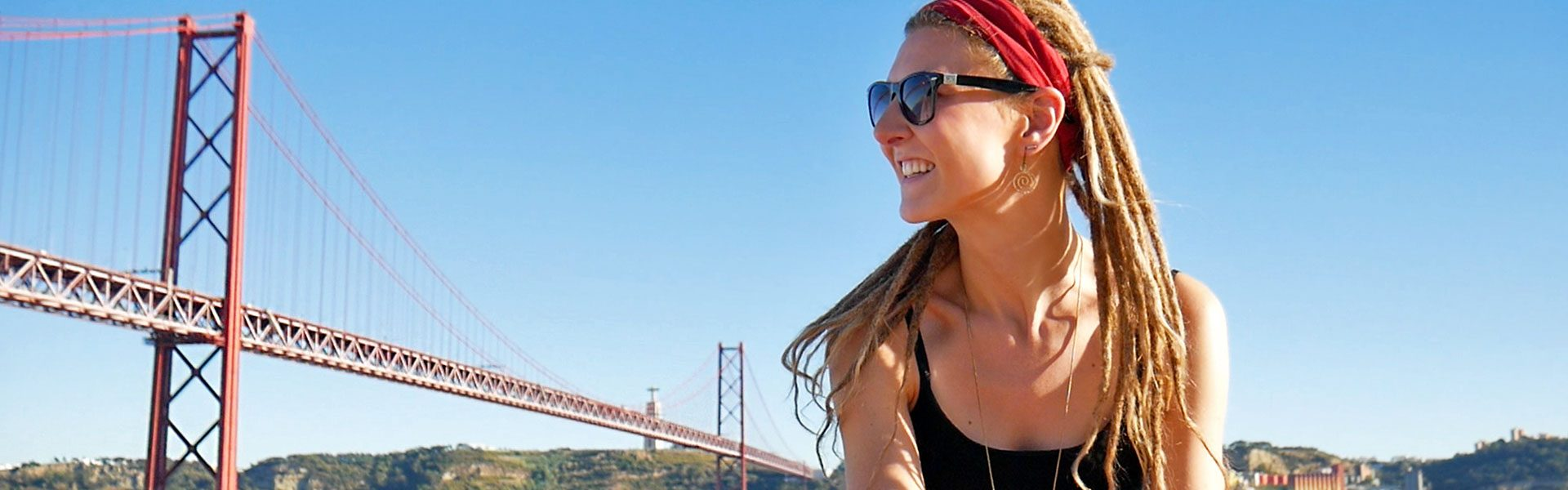 Rasta girl in front of Ponte 25 de Abril and Cristo Redentor in Lisbon, Portugal