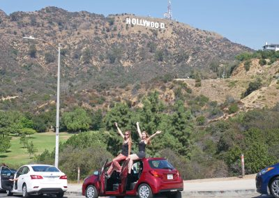 Sisters sitting on red Toyota Yaris with Hollywood Sign in background in LA, CA