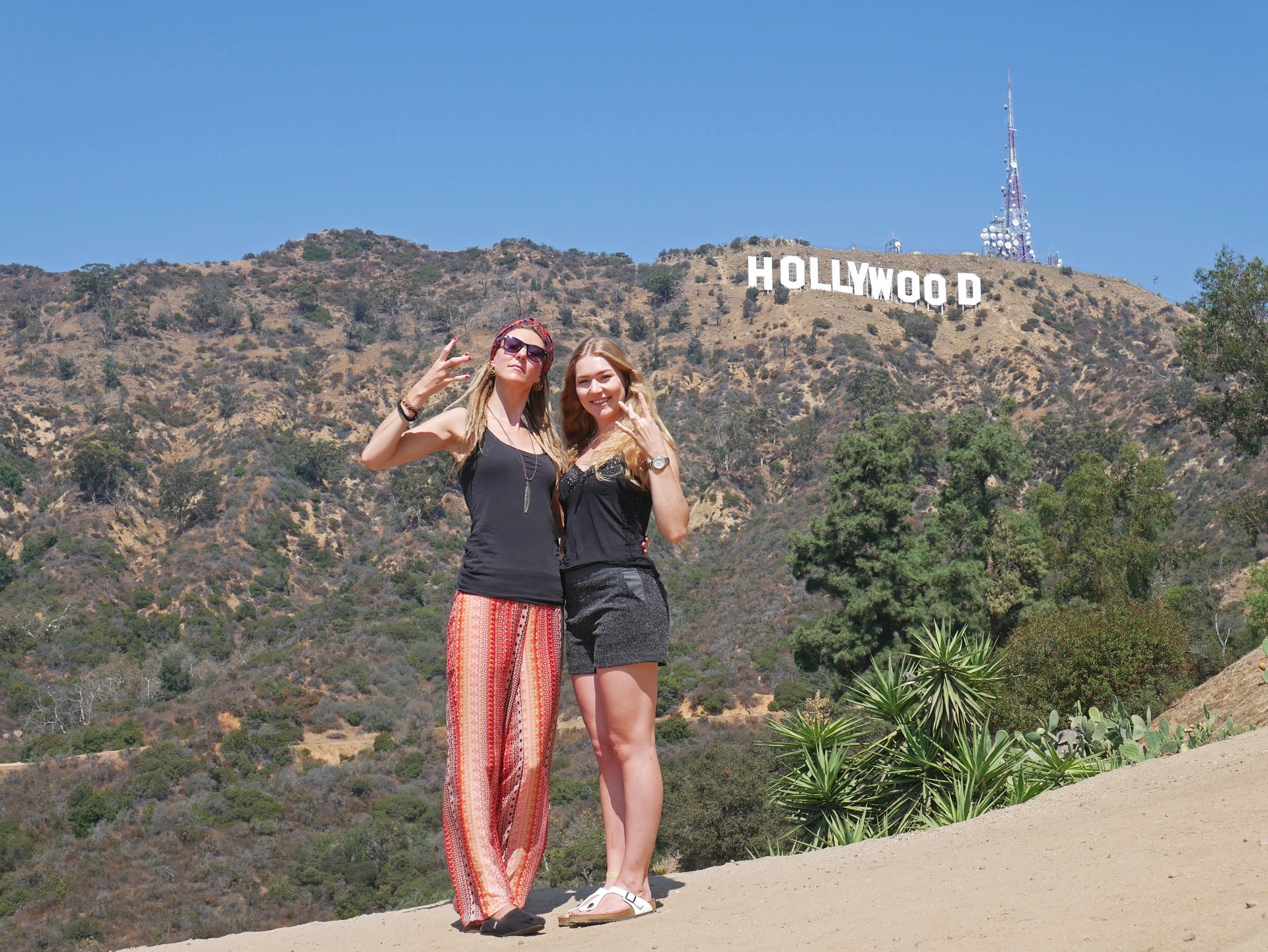 Sisters showing west side hand signs in front of Hollywood Sign in LA, CA