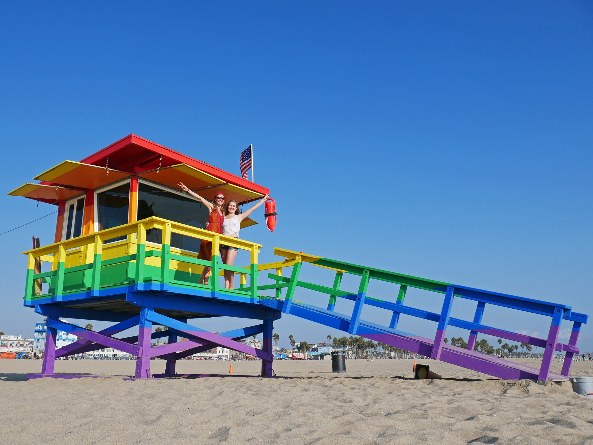Sisters showing peace on Rainbow Lifeguard Tower at Venice Beach in LA, CA