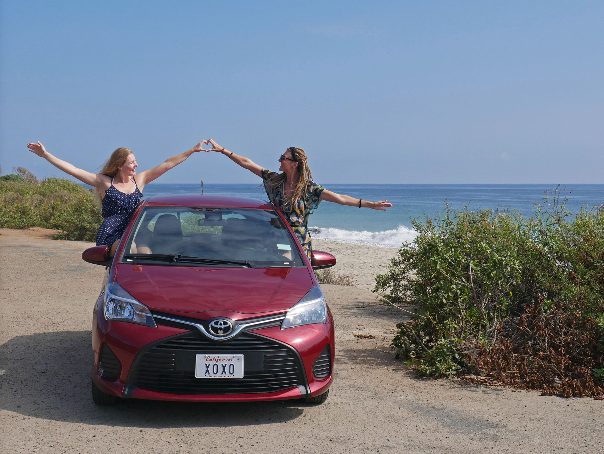 Sisters with red road trip Toyota at Leo Carillo State Beach, Malibu, CA