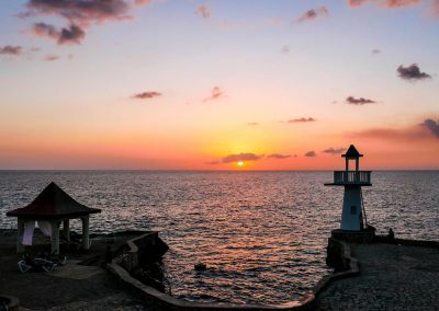 Sunset over ocean with lighthouse on cliffs in foreground in West End, Jamaica