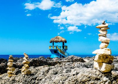 Stacked rocks on cliffs, gazebo and ocean in background in West End, Jamaica