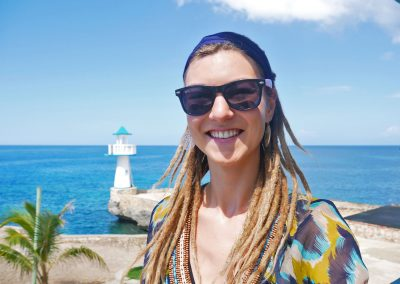 Dreadlock girl on cliff side building with lighthouse and ocean in background in West End, Jamaica