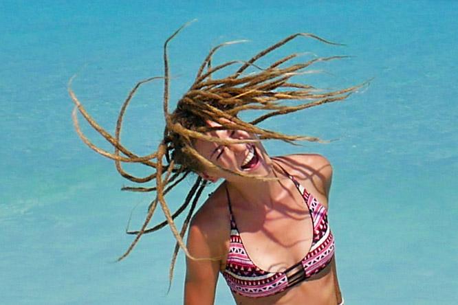 Blonde rasta girl spinning dreads around at Varadero Beach, Cuba