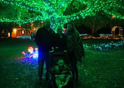 Family under illuminated oak tree at Botanical Garden's GardenFest of Lights in Richmond, VA