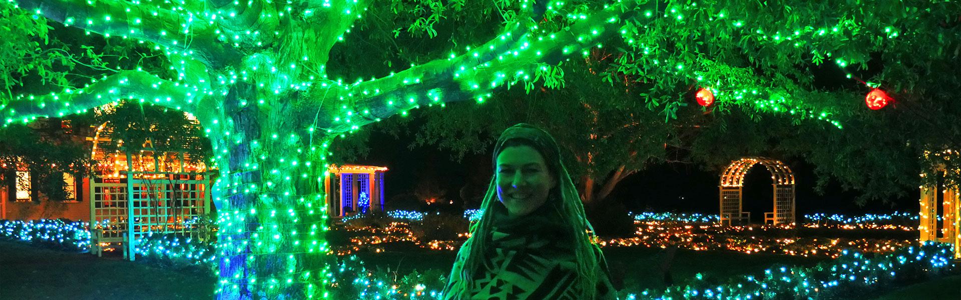 Rasta girl in front of illuminated tree at Gardenfest of Lights in Richmond, VA