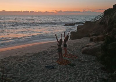 Sisters doing Yoga in front of sunset sky at La Jolla beach in San Diego, CA
