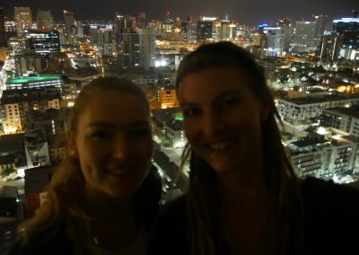Sisters in front of downtown San Diego, CA, skyline at night