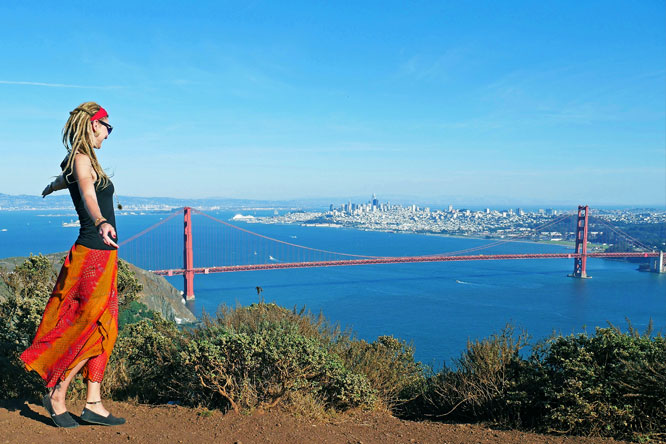 Rasta girl at Marin Headlands overlooking Golden Gate Bridge, city and San Francisco Bay