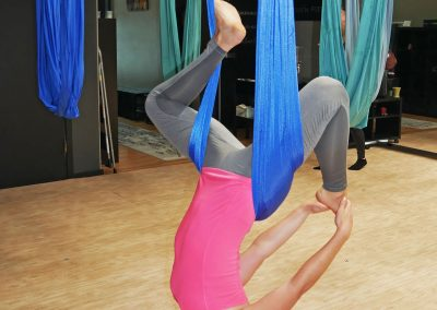 Girl doing upside down aerial yoga pose in hammock at studio in San Francisco, CA