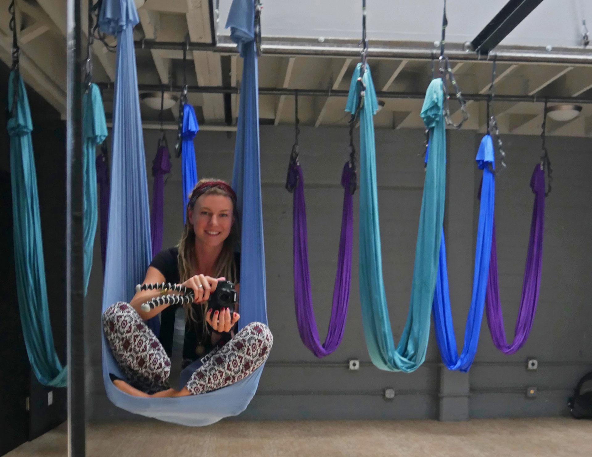 Rasta girl in aerial yoga hammock at studio in San Francisco, CA