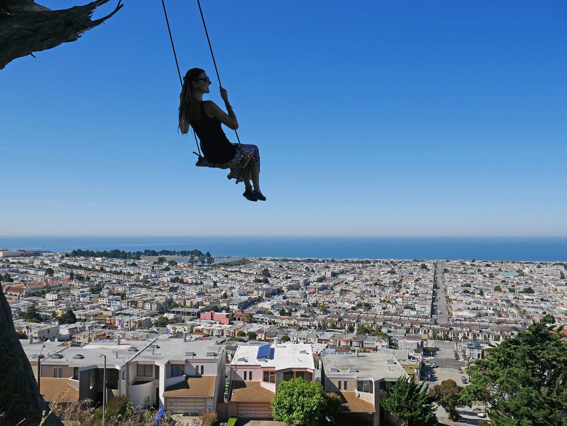 Rasta girl swinging over San Francisco, CA, at Grandview Park