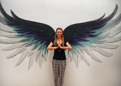 Rasta girl in front of wings mural at yoga studio in San Fran, CA