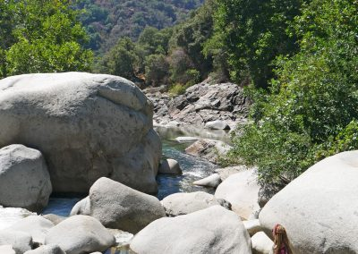 Rasta girl sitting next to Middle Fork Kaweah River in Sequoia National Park