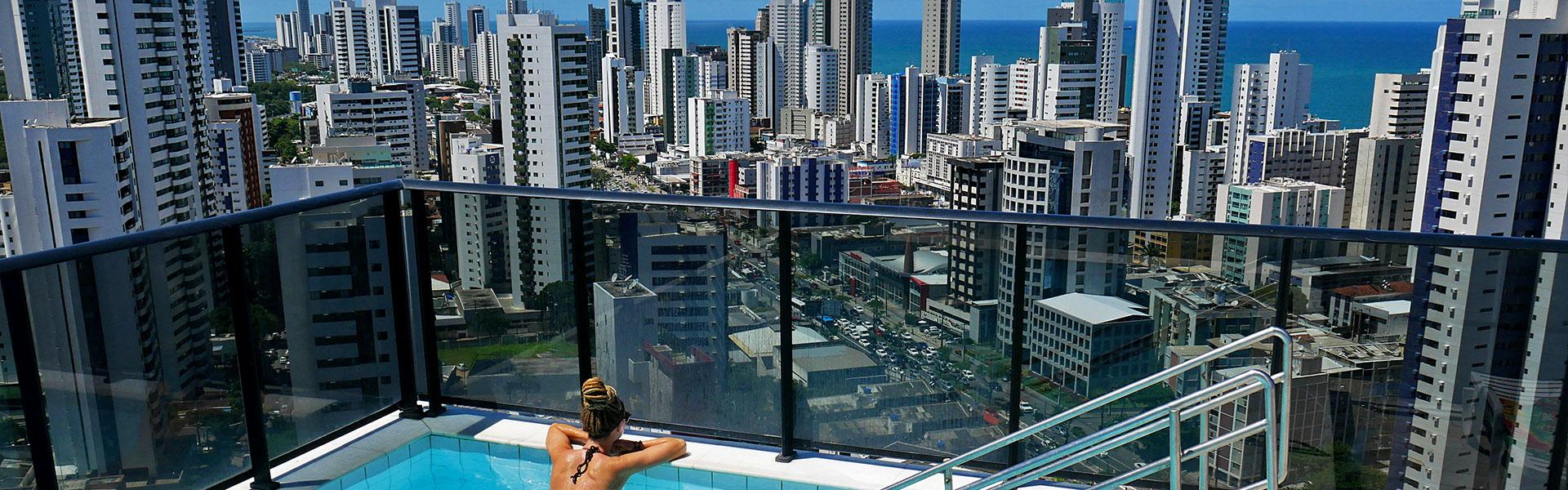 Rasta girl in Airbnb rooftop pool overlooking the city and ocean in Recife, Brazil