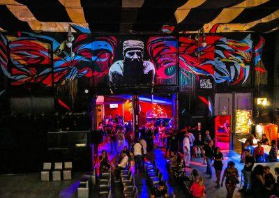 Room at Fábrica de Arte Cubano with mural, bar and party guests in Havana, Cuba