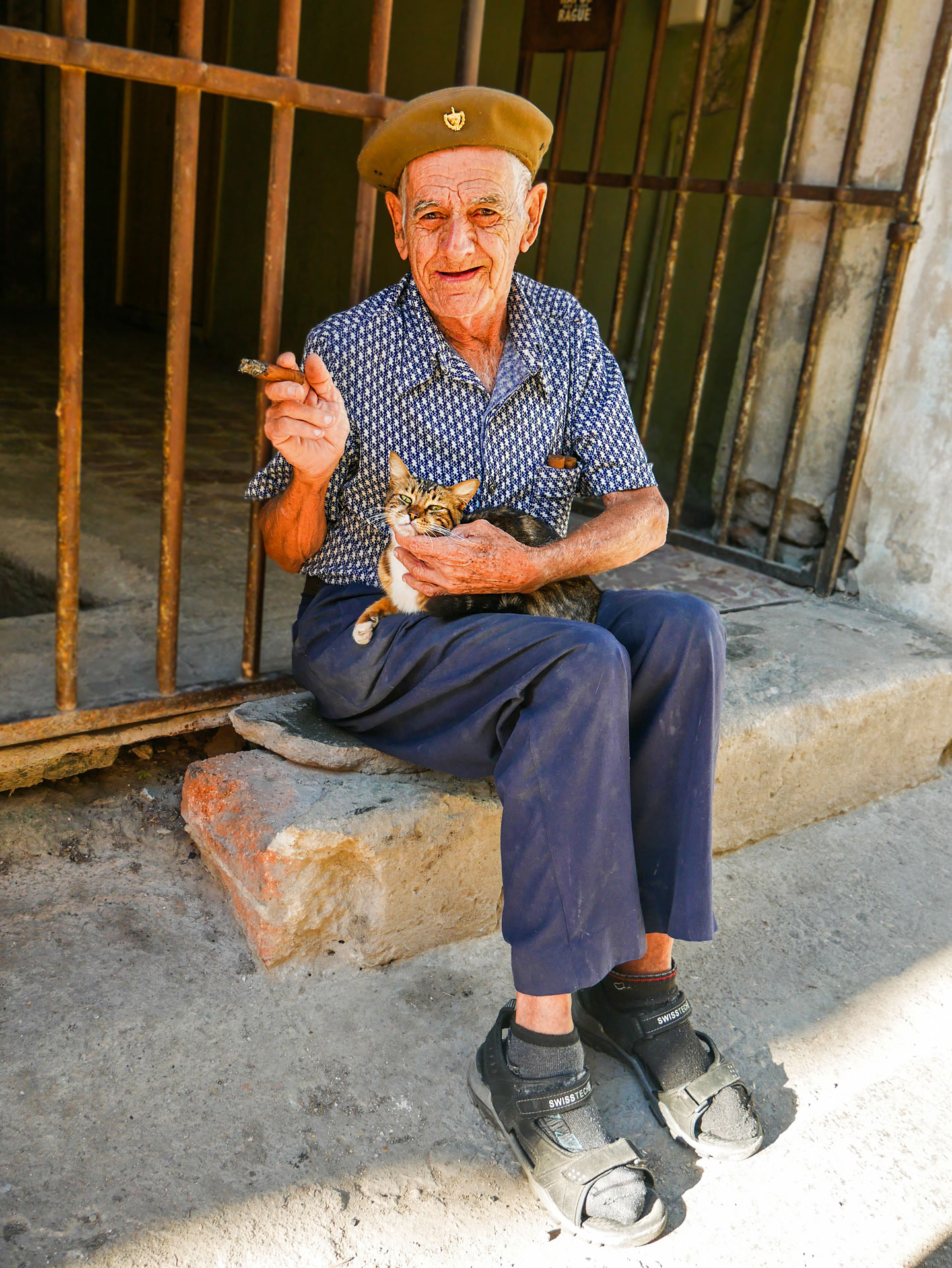 Old man smoking a cigar and petting a cat in street in Havana, Cuba
