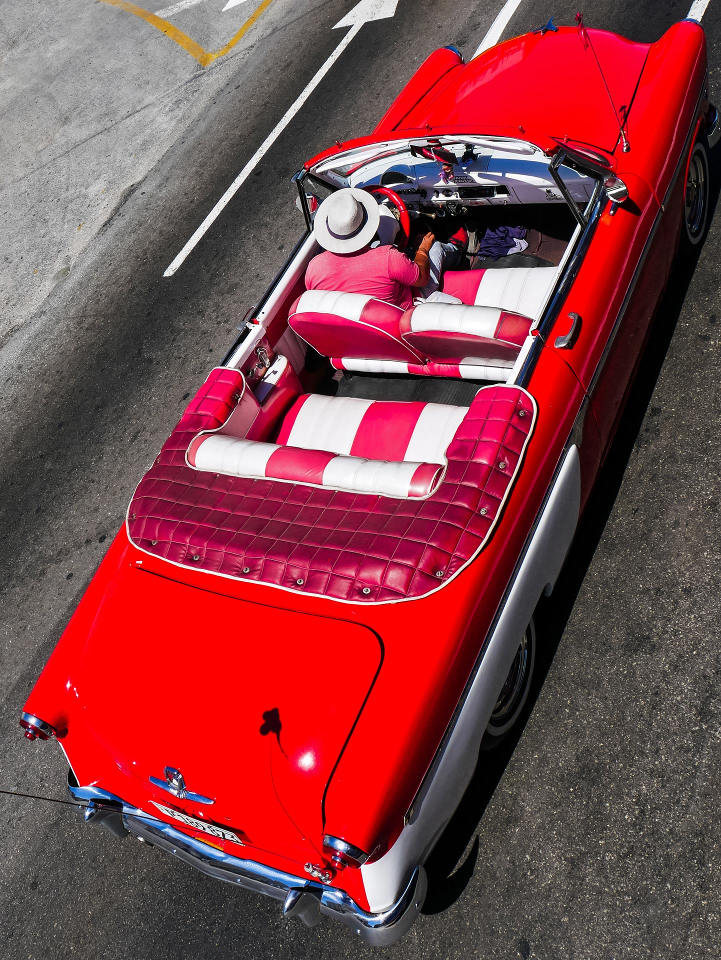 Diver with hat and outfit matching his red classic car in Havana, Cuba
