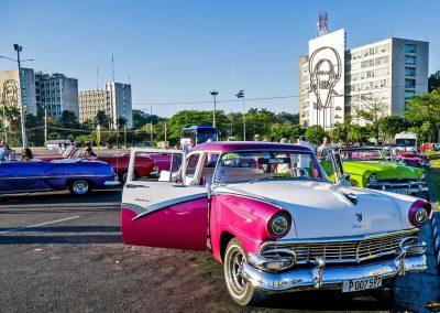 Classic cars at Plaza de la Revolucion in Havana, Cuba, with memorials of Che Guevara and Camilo Cienfuegos in background
