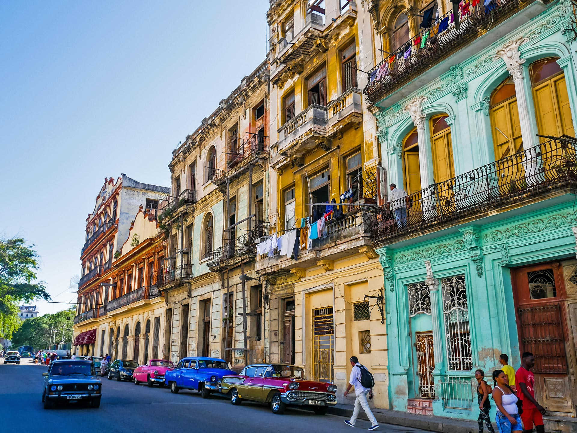 Street with colorful houses, classic cars and people walking in Havana, Cuba