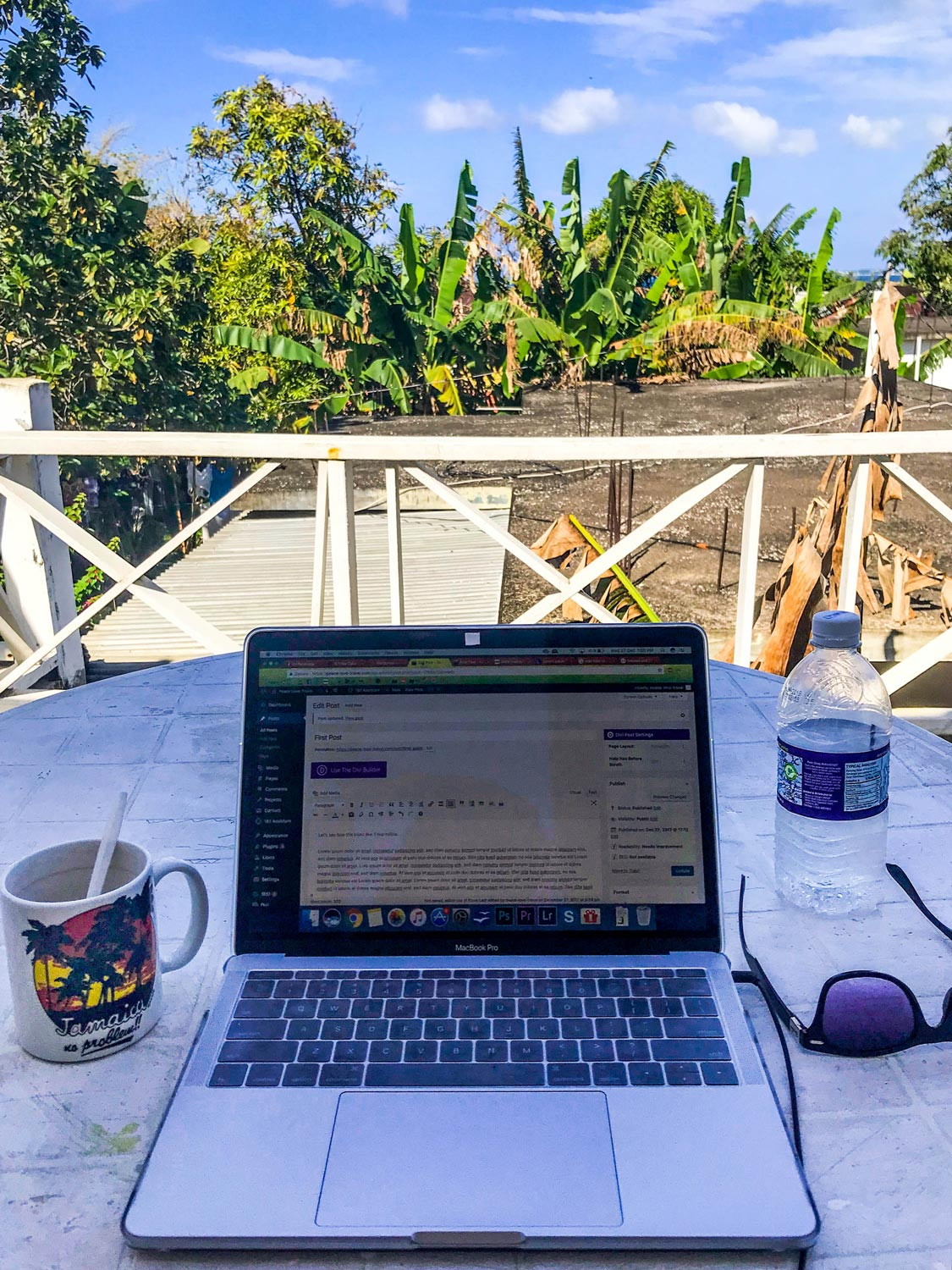Laptop, tea cup and sunglasses on table with view of palmtrees and blue sky in West End, Jamaica