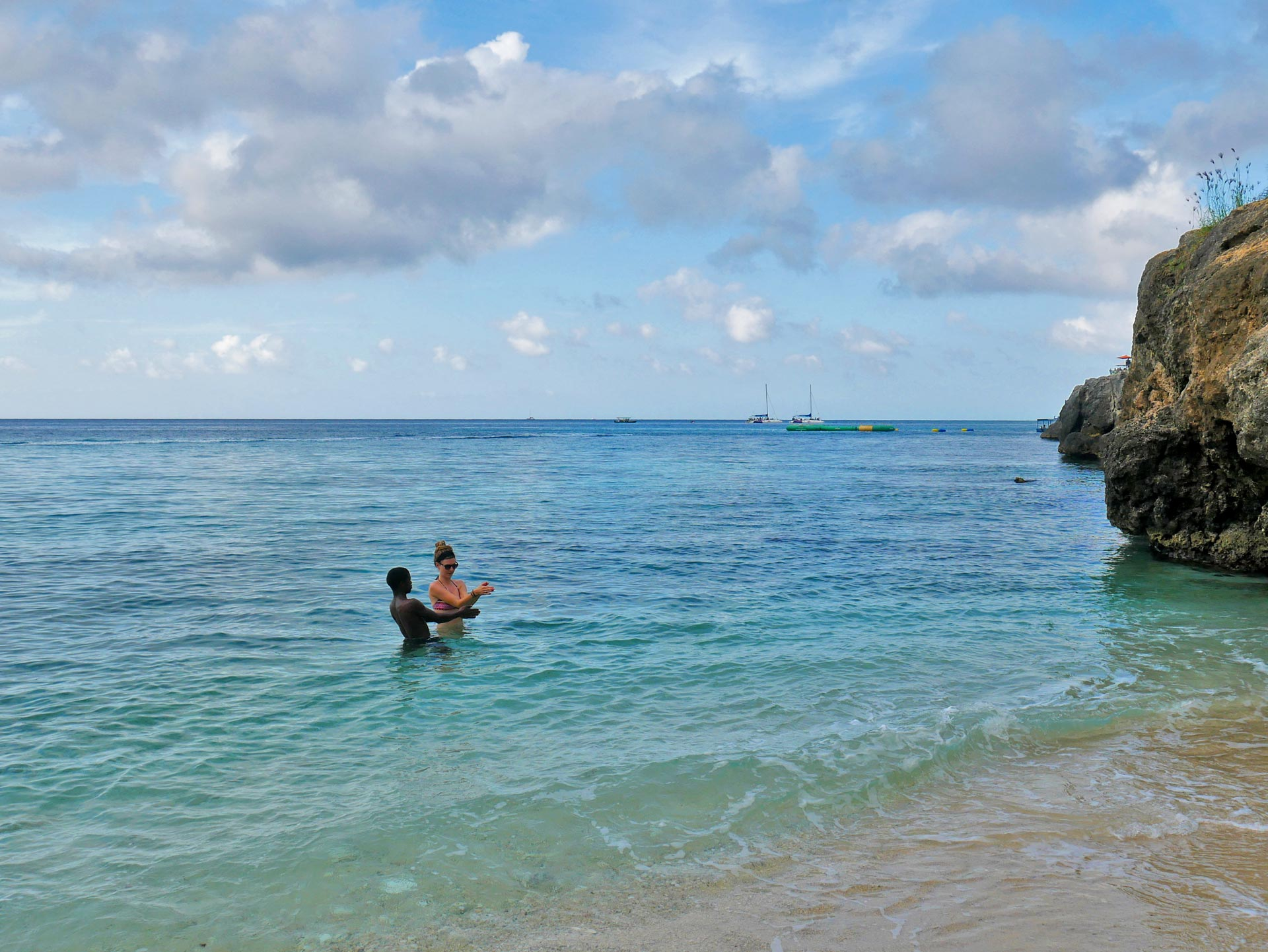 Blonde rasta girl teaching jamaican how to swim in Montego Bay, Jamaica