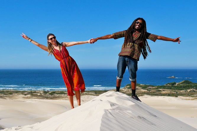 Travel couple on Dunas da Ribanceira with ocean view in Imbituba, Brazil