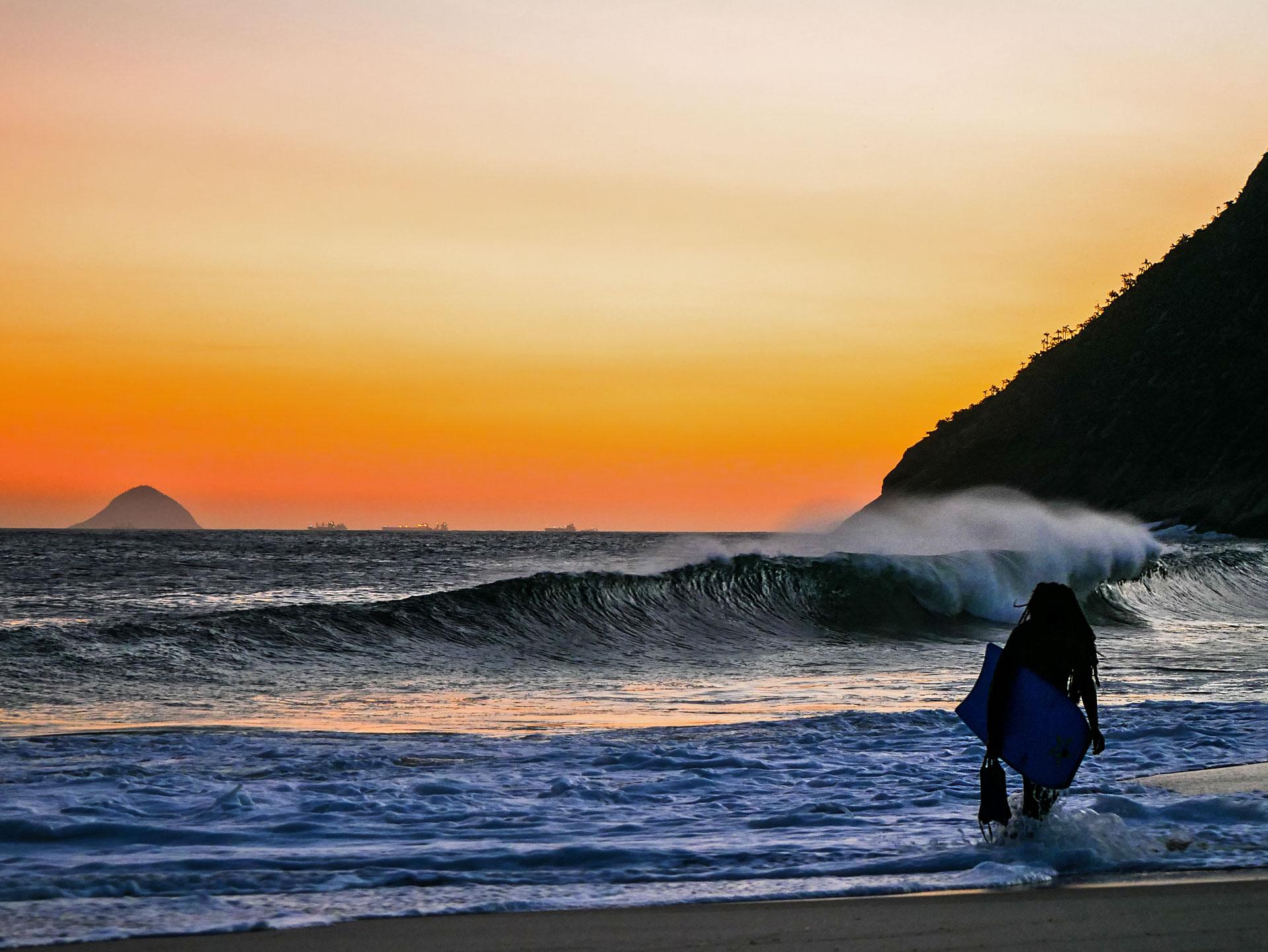 Rasta bodyboarder watching sunset at Itacoatiara beach, Brazil