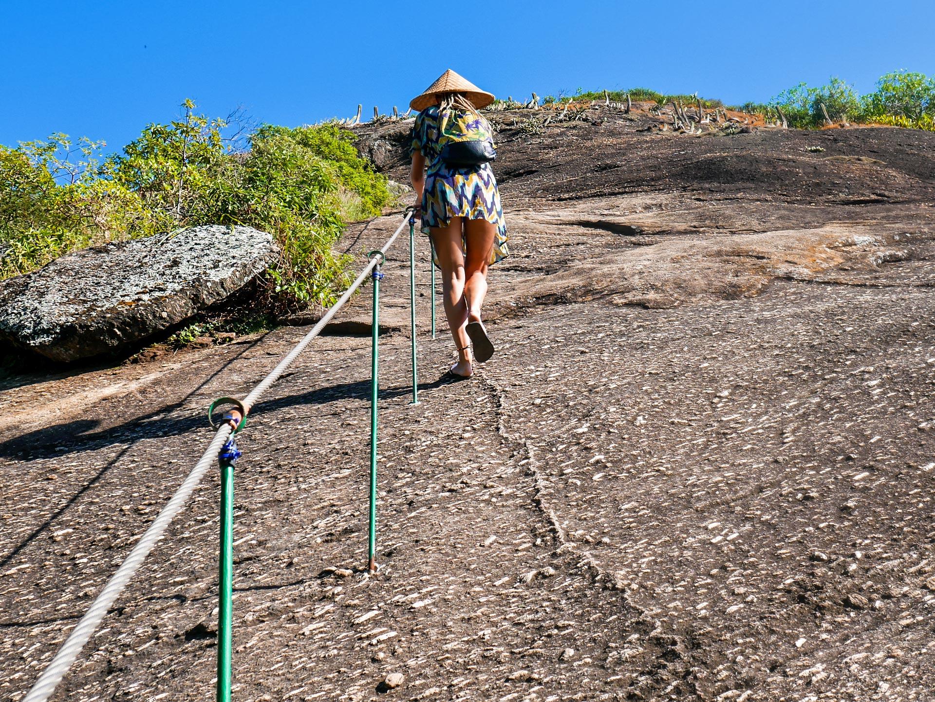 Rasta girl climbing up mountain in Itacoatiara, Brazil