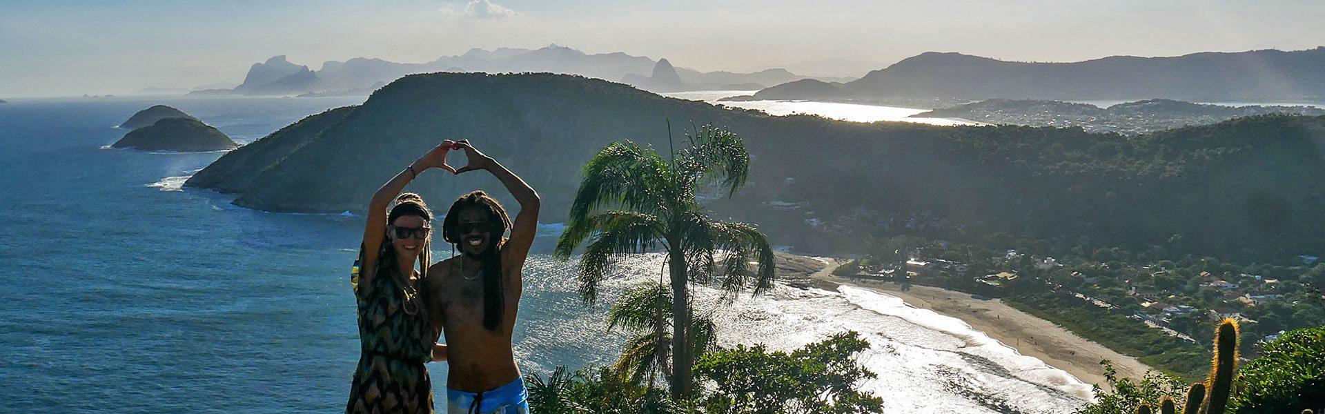 Rasta couple on mountain in Itacoatiara in Niterói, Brazil