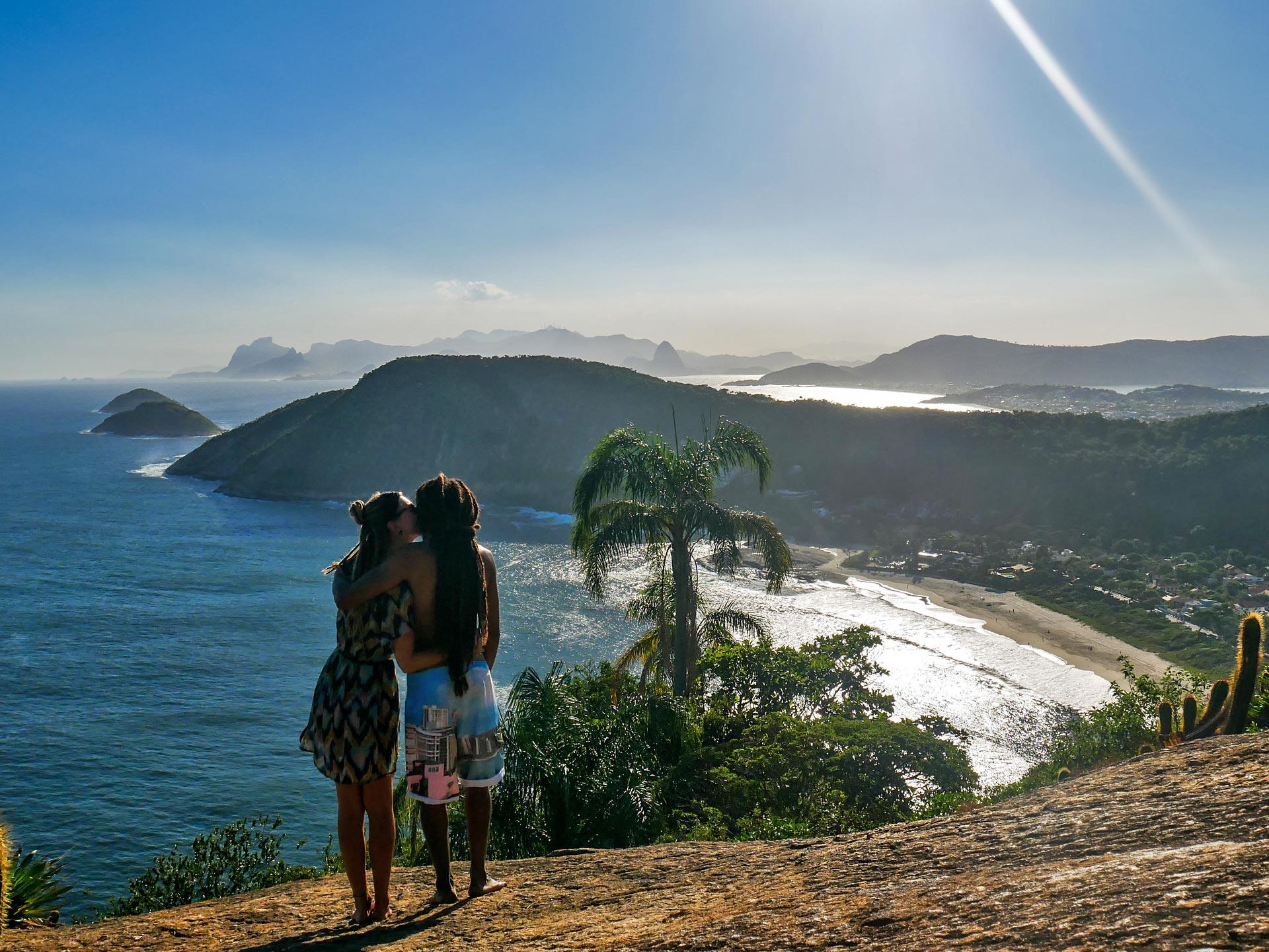 Rasta couple overlooking Itacoatiara on mountain in Serra da Tiririca State Park, Brazil