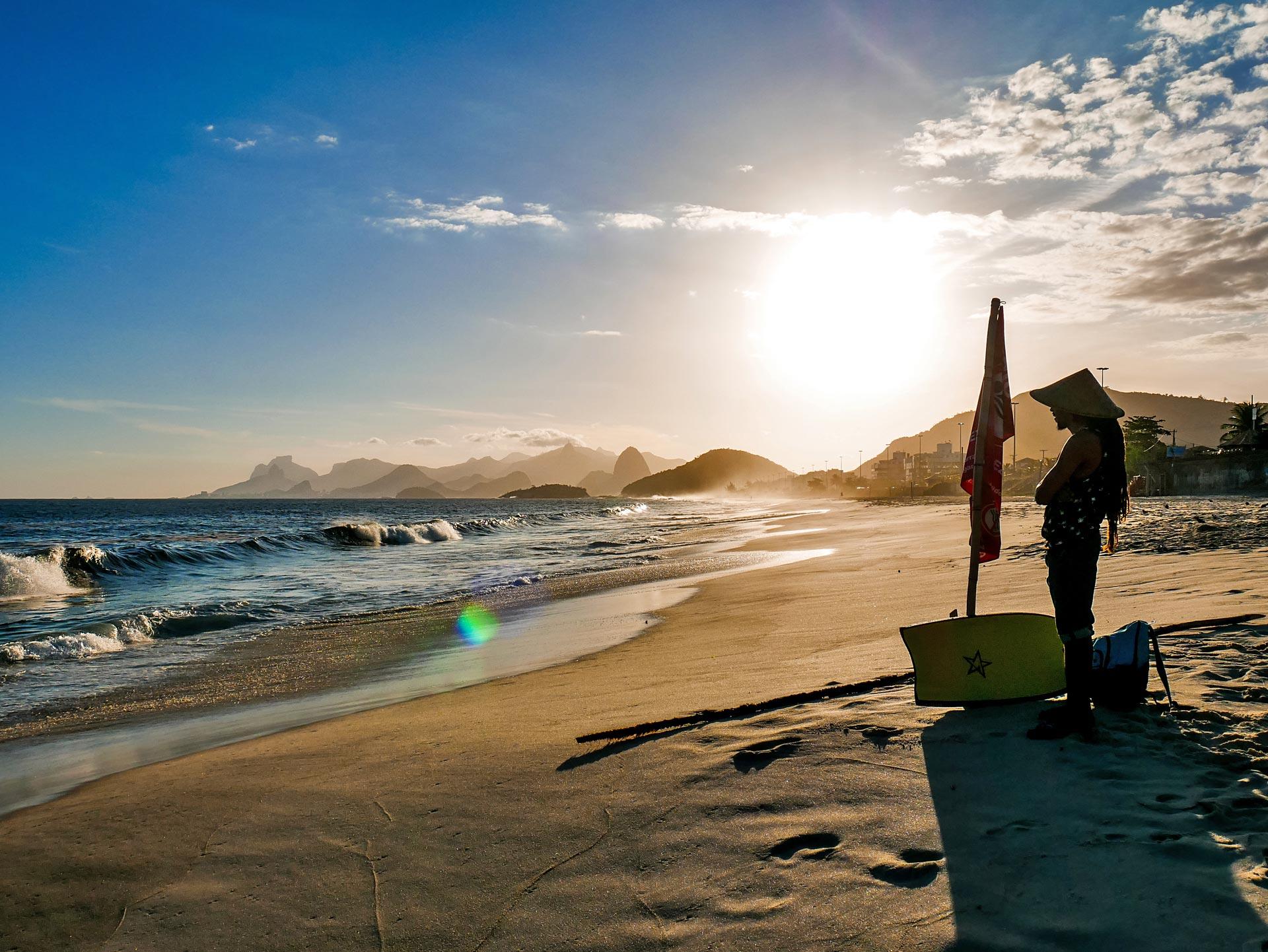 Rasta bodyboarder watching waves from Piratininga beach in Niterói, Brazil