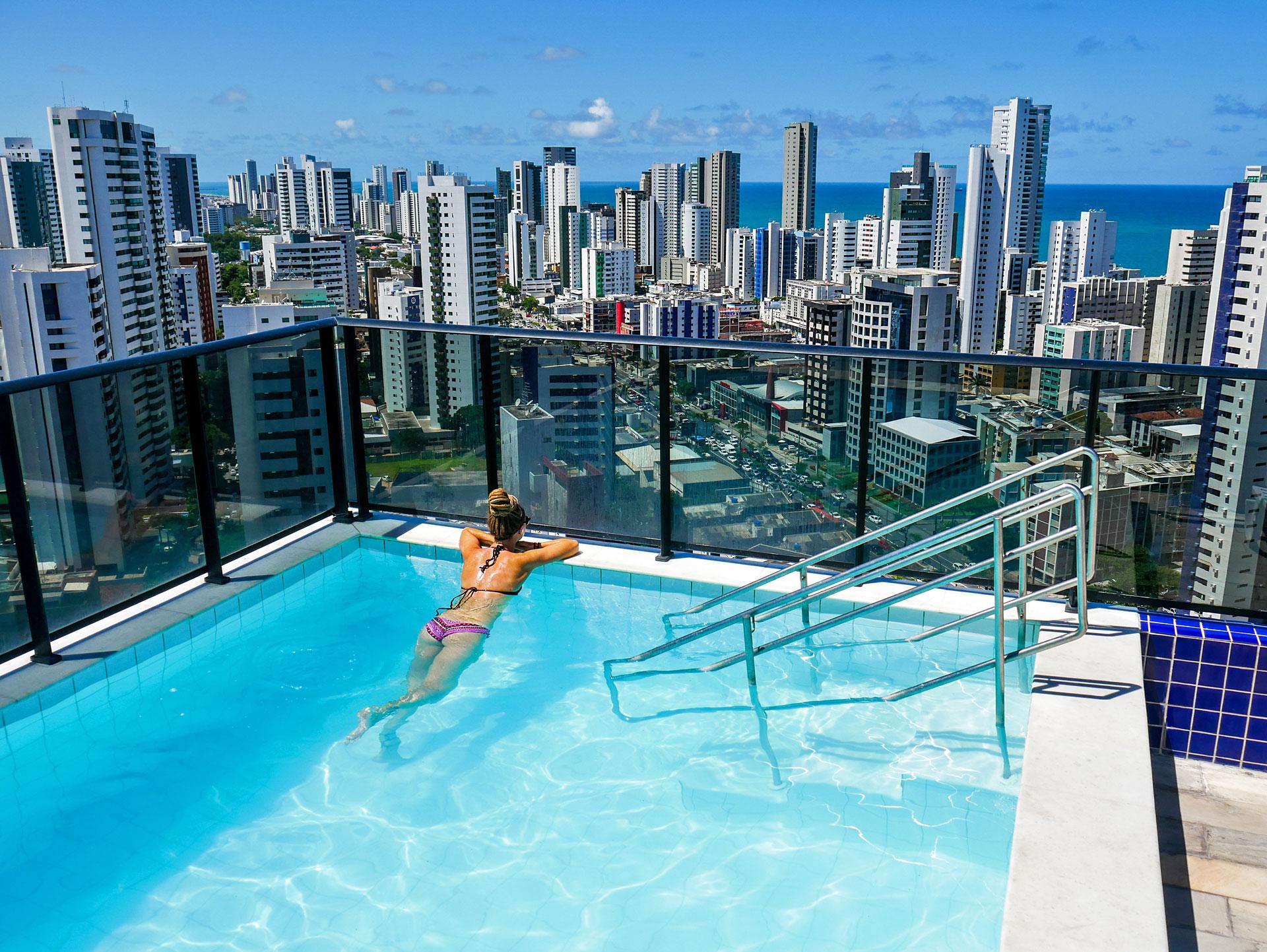 Rasta girl in rooftop pool overlooking Boa Viagem in Recife, Brazil