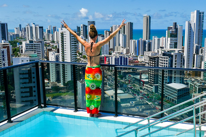 Rasta girl on rooftop overlooking Boa Viagem and ocean in Recife, Brazil