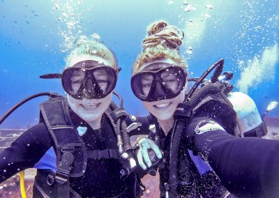 Selfie of scuba diving sisters, smiling without demand valves in Bay of Pigs, Cuba
