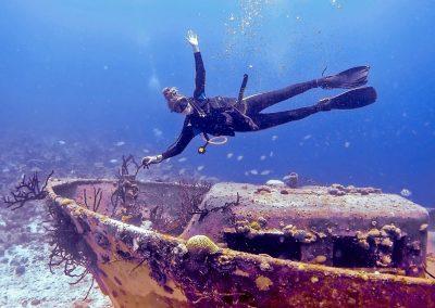 Scuba diving rasta girl above wreck at Bay of Pigs in Cuba