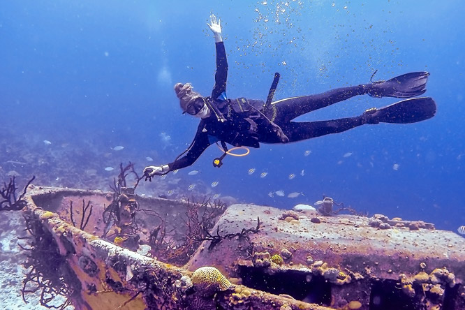 Scuba diving rasta girl above wreck in Cuba