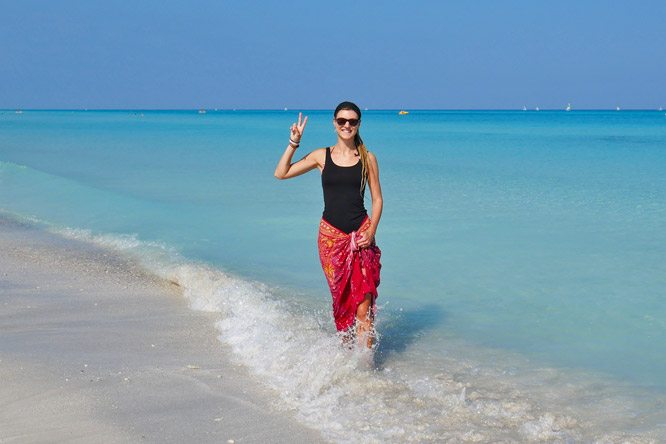 Dreadlock girl showing peace sign at Varadero beach, Cuba