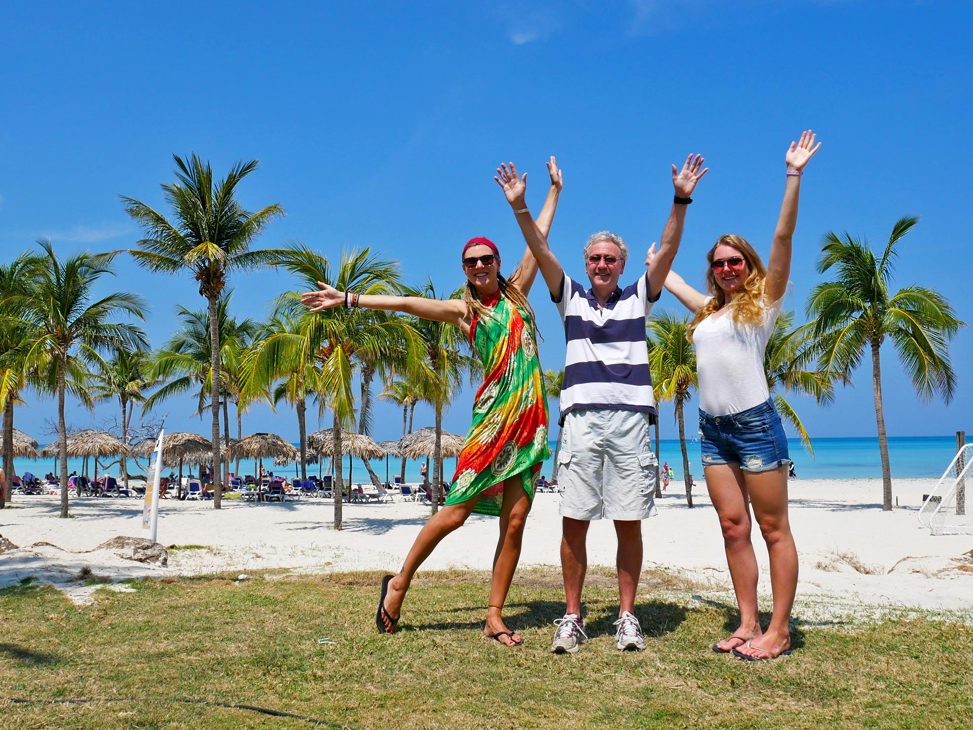 Family in front of beach and palmtrees in Varadero, Cuba