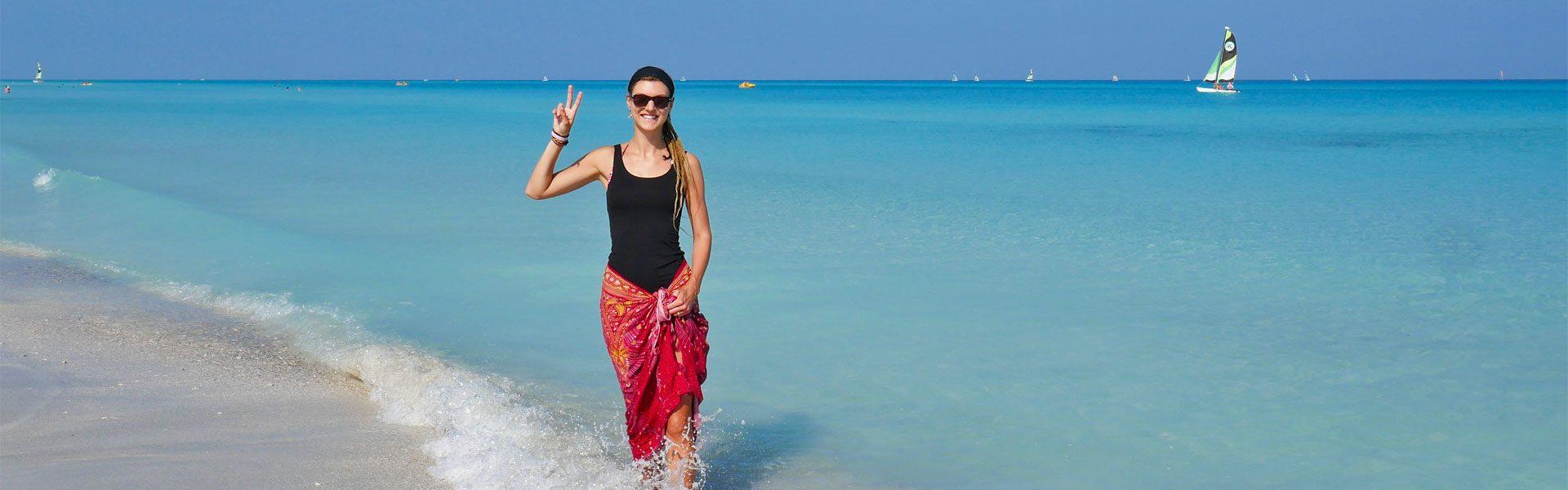 Rasta girl showing peace sign at Varadero beach, Cuba
