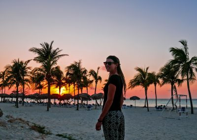 Rasta girl with sunset sky and palm trees in background at Varadero beach, Cuba
