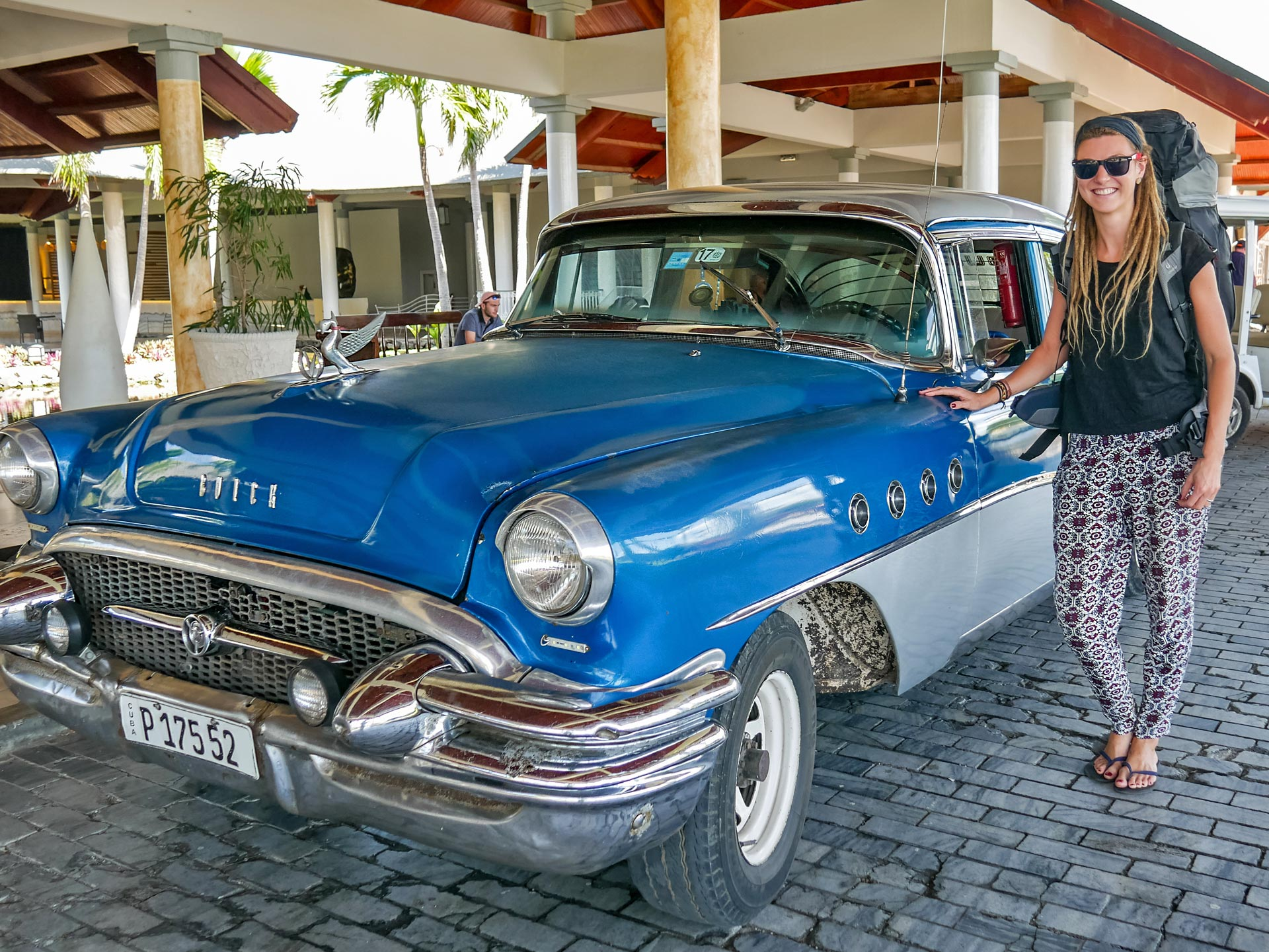 Dreadlock girl in hotel next to classic Buick car in Varadero, Cuba